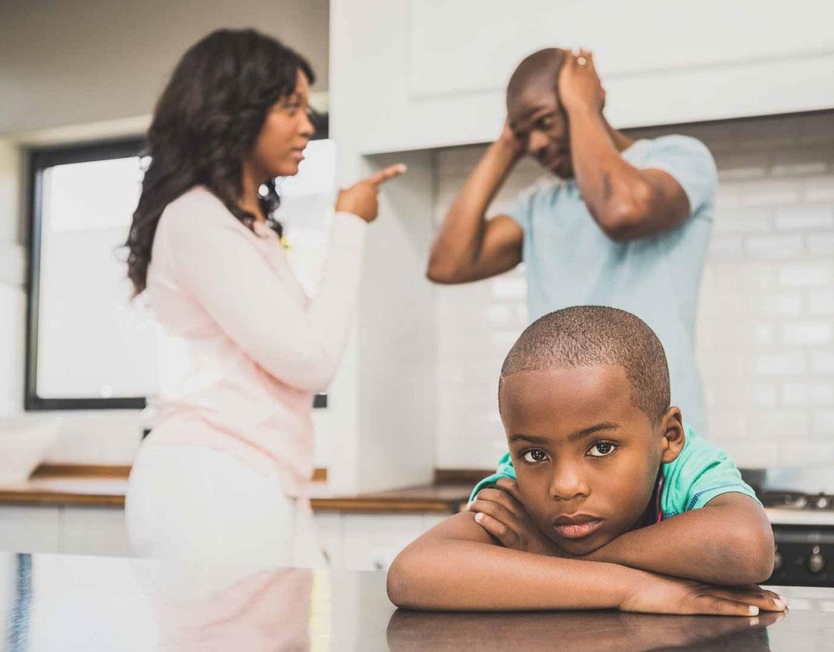 sad child crossing hands while parents argue