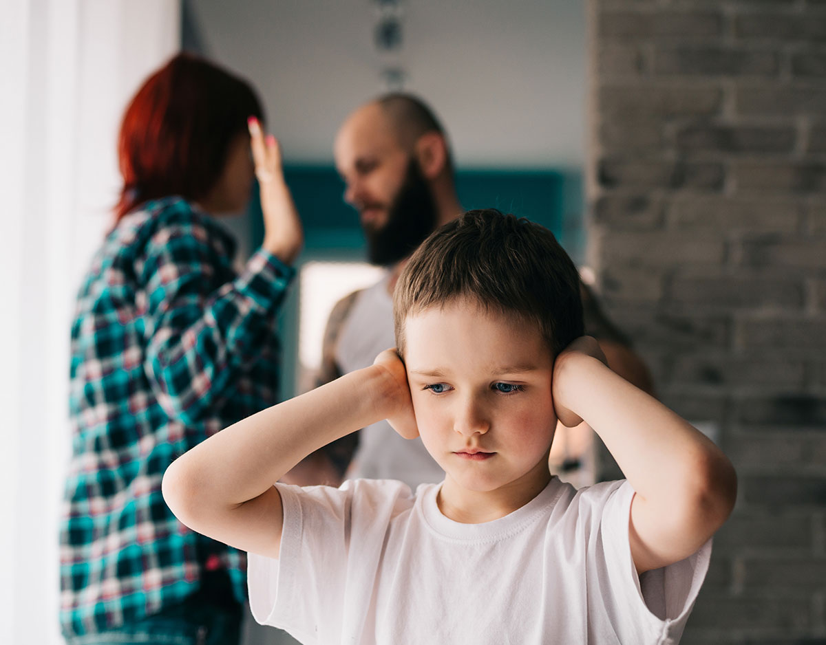 kid covering ears from parents fighting